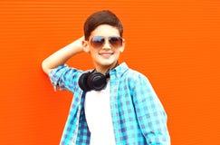 Szczęśliwa uśmiechnięta dziecko chłopiec w okulary przeciwsłoneczni i bezprzewodowi hełmofony zdjęcia royalty free