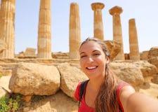 Szczęśliwa uśmiechnięta kobieta bierze jaźń portret z grecką świątynią na tle w dolinie świątynie przy Agrigento, Włochy fotografia stock