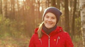 Szczęśliwa Uśmiechnięta kobieta Cieszy się naturę Stać w jesień parku Młody ładny żeński ono uśmiecha się przy kamerą zbiory