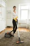 Szczęśliwa uśmiechnięta kobieta czyści dywan zdjęcie royalty free