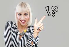 Szczęśliwa uśmiechnięta kobieta patrzeje pisać rysunki znak zapytania zdjęcie stock