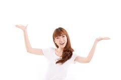 Szczęśliwa, uśmiechnięta kobieta podnosi jej oba ręki, pokazuje coś fotografia stock