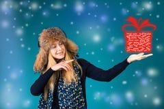 Szczęśliwa uśmiechnięta kobieta pokazuje wskazujący na pudełku z rabatami 50%, 30%, 20% Zima sprzedaży pojęcie Obraz Stock