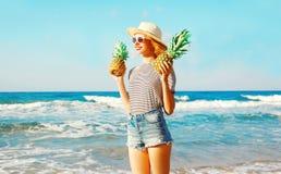 Szczęśliwa uśmiechnięta kobieta trzyma dwa ananasa nad dennym tłem Obrazy Royalty Free
