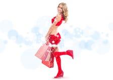 Szczęśliwa uśmiechnięta kobieta w Santa Claus odziewa z torbami Fotografia Royalty Free