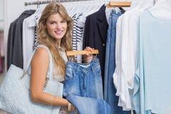 Szczęśliwa uśmiechnięta kobieta wybiera niektóre odziewa Fotografia Royalty Free
