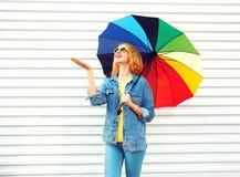 Szczęśliwa uśmiechnięta kobieta z kolorowym parasolem, czeki pada na bielu fotografia stock