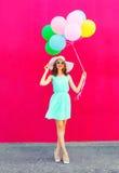 Szczęśliwa uśmiechnięta kobieta z lotniczy kolorowi balony chodzi nad różowym tłem zdjęcie stock