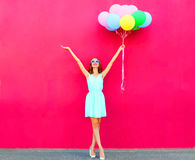Szczęśliwa uśmiechnięta kobieta z lotniczy kolorowi balony nad różowym tłem fotografia royalty free