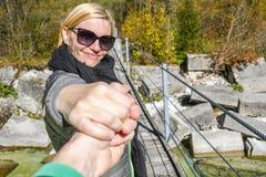 Szczęśliwa uśmiechnięta kobiety pozycja na starym drewnianym wiszącym moście podczas gdy trzymający rękę obrazy royalty free