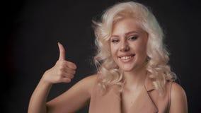 Szczęśliwa, uśmiechnięta młoda blondynka, pokazująca kciuki w geście, odizolowana na czarnym tle zbiory wideo
