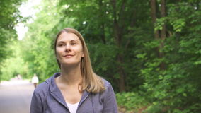 Szczęśliwa uśmiechnięta młoda kobieta chodzi wokoło w pogodnym parku na lata ` s dniu w hoodies zdjęcie wideo
