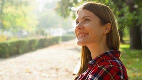 Szczęśliwa uśmiechnięta młoda kobieta cieszy się naturę Siedzieć na ławce w zieleń parku Wolności samotności pojęcie zbiory