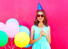 Szczęśliwa uśmiechnięta młoda kobieta w urodzinowej nakrętce z lotniczy kolorowi balony i lizak na kiju nad różowym tłem fotografia stock