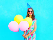 Szczęśliwa uśmiechnięta młoda kobieta w urodzinowej nakrętce z lotniczy kolorowi balony nad błękitem Fotografia Stock