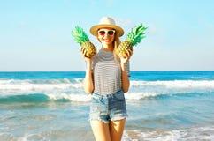 Szczęśliwa uśmiechnięta młoda kobieta z dwa ananasami nad dennym tłem Zdjęcia Royalty Free
