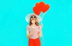 Szczęśliwa uśmiechnięta młoda kobieta z lizakiem, czerwony serce kształtował lotniczych balony w lato słomianym kapeluszu skrótac zdjęcie stock