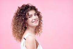 Szczęśliwa uśmiechnięta młoda kobieta z zadziwiającej fryzury połysku kędzierzawym włosy w białej koszula zdjęcie royalty free