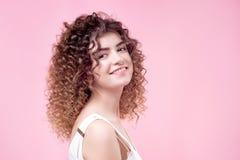 Szczęśliwa uśmiechnięta młoda kobieta z zadziwiającej fryzury połysku kędzierzawym włosy w białej koszula obraz stock
