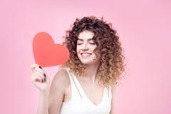 Szczęśliwa uśmiechnięta młoda kobieta z zadziwiającej fryzury połysku kędzierzawym włosy w białej koszula obraz royalty free