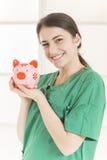 Szczęśliwa uśmiechnięta młoda piękna kobiety lekarka z stetoskopu mienia menchii prosiątka bankiem Obraz Royalty Free