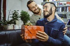 Szczęśliwa uśmiechnięta młoda przystojna homoseksualna para w miłości patrzeje each inną odświętność i daje prezentowi zdjęcie royalty free