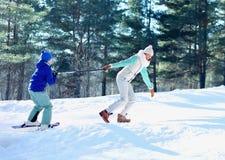 Szczęśliwa uśmiechnięta matka bawić się z syna dziecka narciarstwem w zimie zdjęcie royalty free
