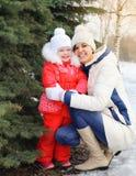 Szczęśliwa uśmiechnięta matka i dziecko blisko choinki w zimie zdjęcia royalty free
