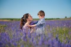 Szczęśliwa uśmiechnięta matka i dziecko wśród kwiatów na lawendy polu Obrazy Royalty Free
