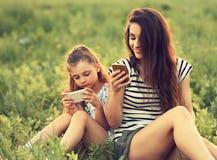 Szczęśliwa uśmiechnięta matka i zabawa żartujemy dziewczyny obsiadanie na zielonym szkle i Zdjęcie Royalty Free
