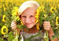 Szczęśliwa uśmiechnięta nastoletnia dziewczyna bawić się z słonecznikiem w polu Fotografia Royalty Free