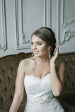Szczęśliwa Uśmiechnięta panny młodej blondynka W Ślubnej sukni antykwarski karło rzeźbiący wewnętrzny luksus Obraz Stock