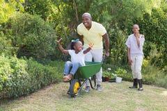 Szczęśliwa uśmiechnięta para bawić się z wheelbarrow i ich córką fotografia royalty free