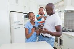 Szczęśliwa uśmiechnięta para z jego babyboy używa cyfrową pastylką Obrazy Stock