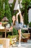 Szczęśliwa uśmiechnięta preteen dziewczyna robi gimnastykom obok dekorującego boże narodzenie stołu wśród cyprysowych drzew w Taj zdjęcia royalty free