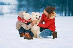 Szczęśliwa uśmiechnięta rodzina ma zabawę w wpólnie zima dnia, matki i dziecka odprowadzeniu z białym Samoyed psem, obrazy royalty free