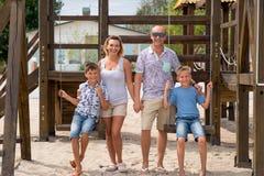 Szczęśliwa uśmiechnięta rodzina z dwa dziećmi przy playgroun wpólnie Zdjęcie Stock