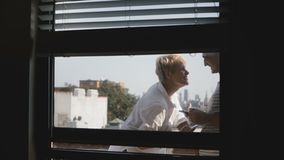 Szczęśliwa uśmiechnięta romantyczna pary pozycja przy małym pogodnym balkonem, widok przez mieszkania okno, używać smartphones zbiory