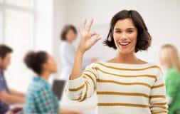 Szczęśliwa uśmiechnięta studencka dziewczyna pokazuje ok przy szkołą obrazy stock