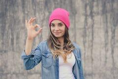 Szczęśliwa ufna uśmiechnięta kobieta bez makijażu ubierał w cajg koszula, biały kapelusz z długi kędzierzawym, słucha pokazywać z fotografia stock