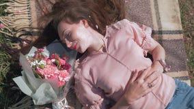 Szczęśliwa urocza kobieta kłama blisko pięknego bukieta kwiaty na bedspread na gazonie i cieszy się plenerowego odtwarzanie, odgó zbiory