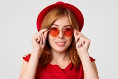 Szczęśliwa urocza młoda kobieta modeluje w studiu, jest ubranym czerwonych cienie, kapelusz i bluzka, jej swój styl, patrzeje ele obrazy royalty free