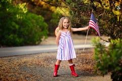 Szczęśliwa urocza mała dziewczynka uśmiecha się flaga amerykańskich outs i macha zdjęcie royalty free