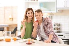 Szczęśliwa urocza para ma śniadanie z smakowitym chlebem przy stołem w kuchni fotografia royalty free