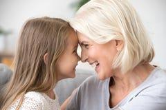 Szczęśliwa w średnim wieku babcia i mały wnuczki macanie ostrożnie wprowadzać zdjęcia royalty free