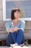 Szczęśliwa w średnim wieku kobieta siedzi outside w cajgach Zdjęcie Royalty Free