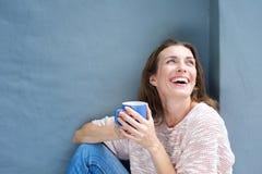Szczęśliwa w połowie dorosła kobieta śmia się z filiżanką herbata Obrazy Royalty Free
