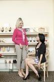 Szczęśliwa w połowie dorosła kobieta próbuje na piętach podczas gdy dojrzały żeński patrzeć w obuwianym sklepie Obraz Stock