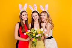 Szczęśliwa wielkanoc! Trzy ładny, modne dziewczyny jest ubranym królików ucho na h Zdjęcie Stock