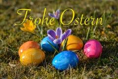 Szczęśliwa wielkanoc w niemiec z kilka kolorowymi Wielkanocnymi jajkami kłama o zdjęcie stock